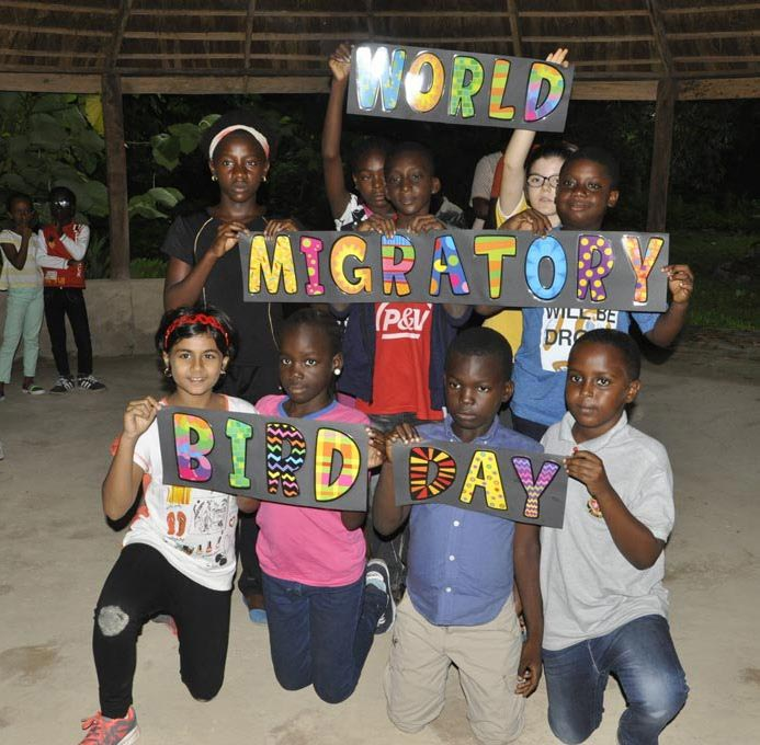 Picture of children holding banners to celebrate World Migratory Bird Day